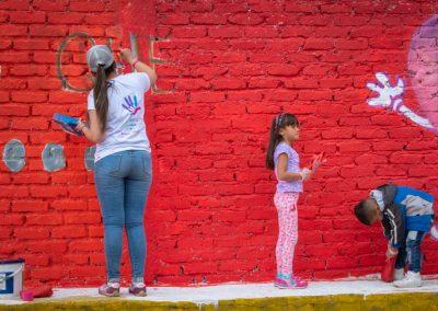 Voluntarios y niños pintando Scotiabank Colpatria